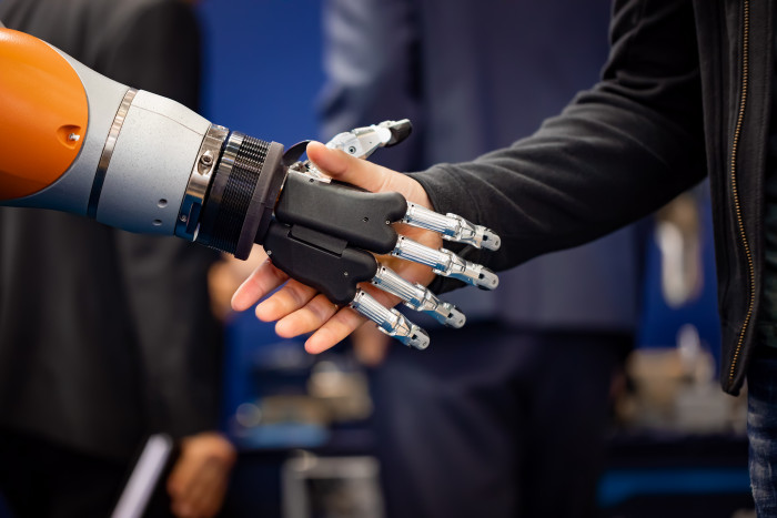hand-of-a-businessman-shaking-hands-with-a-android-QUYJPHR.jpg
